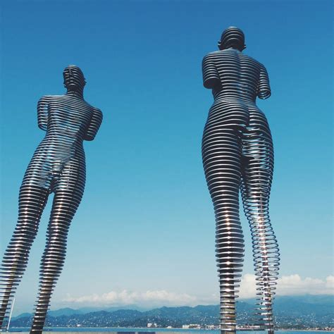 Moving Statues Of A Man And Woman Pass Through Each Other